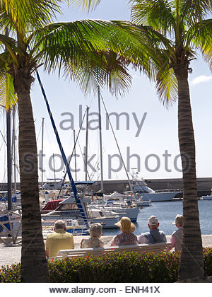 Group of elderly pensioner holidaymakers sitting sunbathing on bench enjoying the marina view at Puerto Calero Lanzarote - Stock Photo