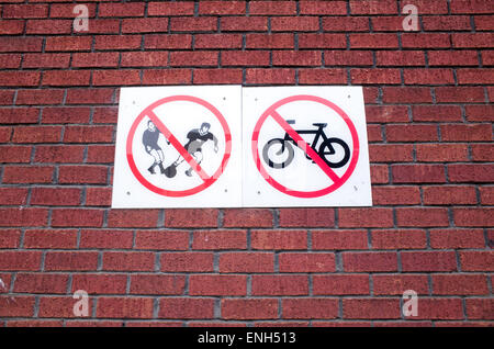 No cycling or ball games signs on a brick wall at a council housing estate, UK - Stock Photo