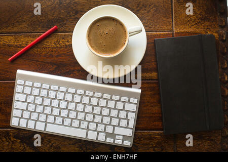 Keyboard, black notebook with pencil and a Cup of coffee, top view of the texture of an old tree. - Stock Photo
