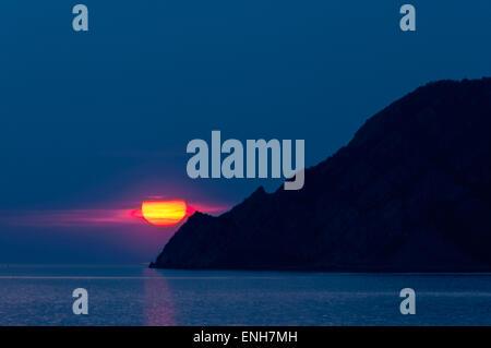 Sun setting over Ligurian Sea near the coast of Manarola, Cinque Terre, Italy - Stock Photo