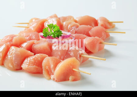 Pieces of raw chicken meat on skewers - Stock Photo
