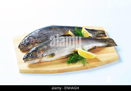 Two fresh trout on a cutting board - Stock Photo