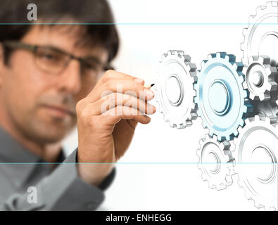 Caucasian engineer drawing gears on a transparent wall. Engineering background concept over white.
