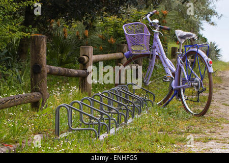 violet bike with basket and  bicycle racks near a wooden fence in a dirt road - Stock Photo