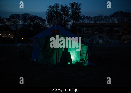 Tundikhel, Kathmandu, Nepal. 4th May, 2015. A woman from dhading village cooking food for her family in a camp at - Stock Photo