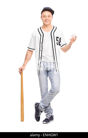 Full length portrait of a young baseball player in a white jersey posing with a bat and a ball isolated on white - Stock Photo