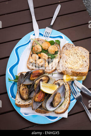 Barbecued scallops and green lipped mussels on bread at an outdoor food shack on the beach at Kaikoura, New Zealand - Stock Photo