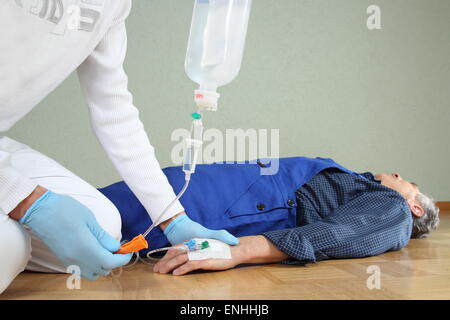 A Emergency service giving a infusion to a patient - Stock Photo