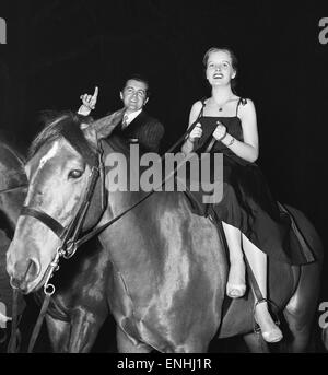 British musician Ronnie Ronalde and Bride Corsie on horseback, taking part in a race around Berkeley Square as part - Stock Photo