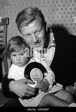Everton football players cut a disc. Jimmy Gabriel,with his daughter holding one of the discs. 4th October 1964. - Stock Photo