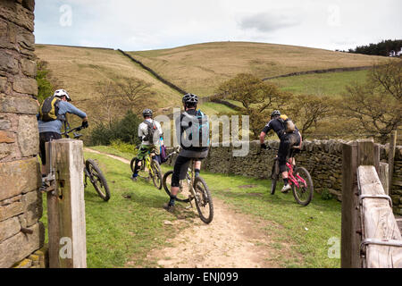 Four mountain bikers having a rest before they continue along the trail in the Derwent Valley in the Peak District - Stock Photo