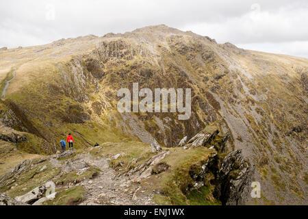 Hikers on Minffordd path to Penygadair (Penygader) summit of Cadair Idris (Cader Idris) mountain range in southern - Stock Photo