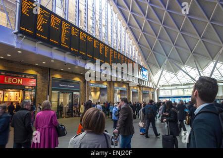 King's Cross railway station is a major London railway terminus. Passengers look at departures board - Stock Photo