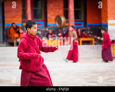 Monks practising a dance for a festival in a monastery courtyard in Lo Manthang, Upper Mustang, Nepal - Stock Photo