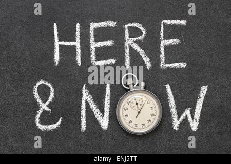 here and now phrase handwritten on chalkboard with vintage precise stopwatch used instead of O - Stock Photo