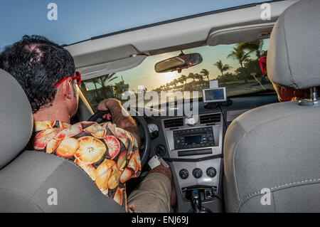 A young adult couple driving along Highway 1 in a convertible sports car. Florida Keys. USA - Stock Photo