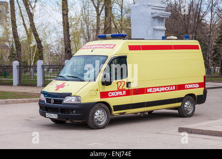 Ambulance car parked up in the street. Text on russian: 'Acute care' - Stock Photo