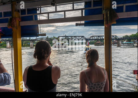 Tourists on a boat floating towards the bridge over the river Kwai. Kanchanaburi. Thailand - Stock Photo