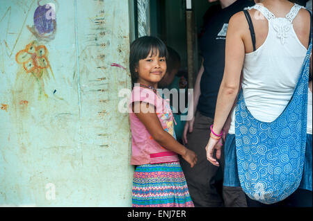 Student volunteers helping a young girl from the orphanage at Sangkhlaburi. Kanchanaburi. Thailand - Stock Photo