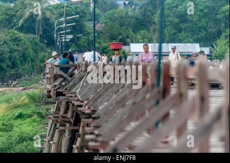 Local people crossing the rickety wooden bridge (Saphan Mon) Sangkhlaburi. Kanchanaburi Province. Thailand. - Stock Photo