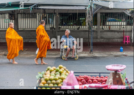 A wheelchair bound begger watches a group of Buddhist monks on their morning alms round. Bangkok. Thailand - Stock Photo
