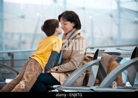 Loving mother and son hugging at airport - Stock Photo