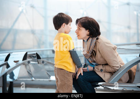 Loving mother and son at airport - Stock Photo