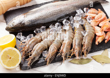Fresh raw sea food with spices on wooden table background - Stock Photo