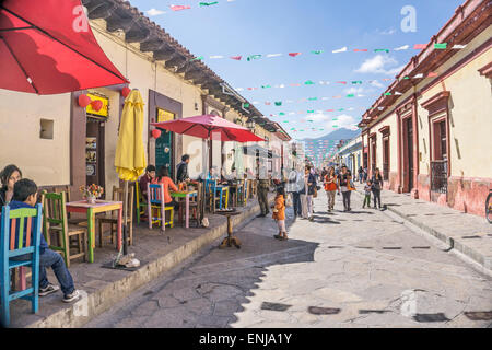 locals tourists & a lone busker enjoy eating al fresco or browsing shops on pedestrian street Real de Guadalupe - Stock Photo