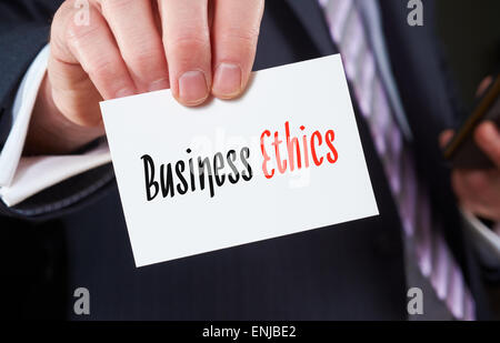 A businessman holding a business card with the words, Business Ethics, written on it. - Stock Photo