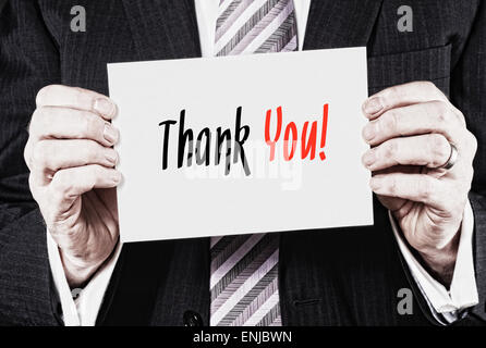 A businessman holding a business card with the words, Thank You, written on it. - Stock Photo