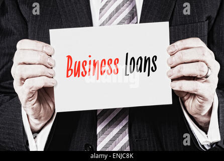 A businessman holding a business card with the words, Business Loans, written on it. - Stock Photo