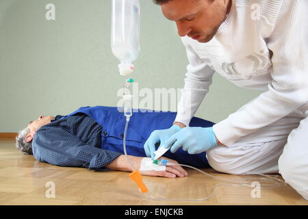 A Infusion of a patient by a paramedic - Stock Photo