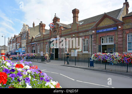 East Ham underground station entrance built on a road bridge above railway lines in East London on the District - Stock Photo