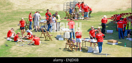 Poppy volunteers work in Tower of London dry moat hot summer day assembling red ceramic poppies to wire stems Blood - Stock Photo