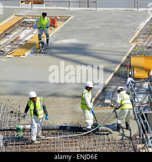 Placing & vibrating pumped concrete into steel reinforcement with power float operator following finishing smooth - Stock Photo