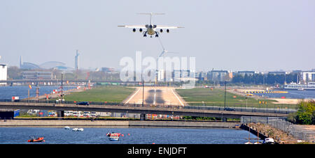 London City Airport four engined passenger jet aircraft approaching runway in middle of old London Docklands waters - Stock Photo