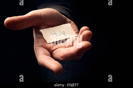 A man holding a card with a hand written message on it, Help. - Stock Photo