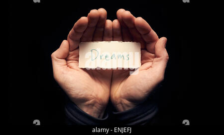 A man holding a card with a hand written message on it, Dreams. - Stock Photo