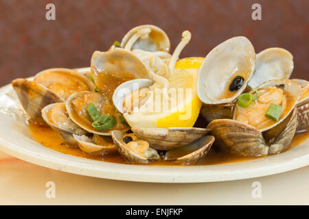 Chinese baby clams sauteed in sweet and spicy black bean sauce with lemon wedge - Stock Photo