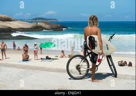 RIO DE JANEIRO, BRAZIL - FEBRUARY 2015: Brazilian surfer on a bike sits looking out at the waves at Arpoador. - Stock Photo