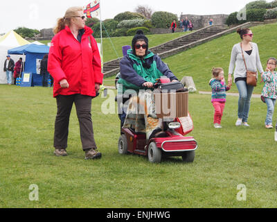 A senior lady rides a mobility scooter across grass. - Stock Photo