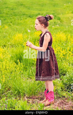 Girl in country meadow blows on dandelion - Stock Photo