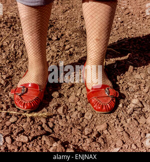 female legs in red loafers on dirty roads - Stock Photo