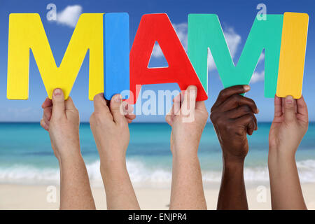 Hands holding the word Miami in summer on sea and beach - Stock Photo