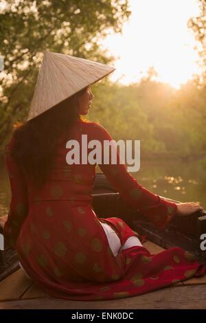 Woman wearing ao dai dress in boat, Can Tho, Mekong Delta, Vietnam, Indochina, Southeast Asia, Asia - Stock Photo