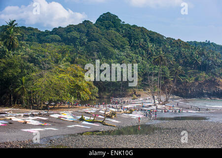 Wet clothes drying on a rocky beach, east coast of Sao Tome, Sao Tome and Principe, Atlantic Ocean, Africa - Stock Photo