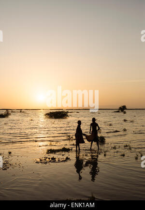 Children of the Dassanech tribe fishing on the shore of Turkana Lake, Omo Valley, Ethiopia, Africa - Stock Photo