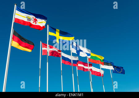 Baltic European national flags flying on a sunny day at the seafront promenade of Warnemünde, Rostock, Germany, Europe