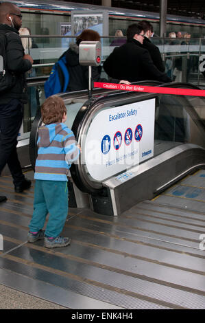 boy at top of escalators Kings Cross railway station London - Stock Photo